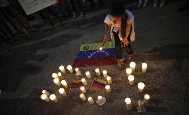 Girl lighting SOS Venezuela candles