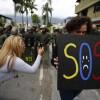 SOS sign held by Venezuelan protester